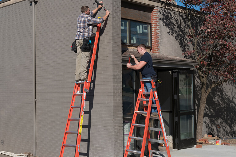 two men standing on 2 different types of ladders
